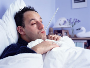Man in bed with thermometer in his mouth
