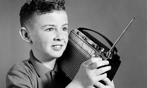 Black and white image of a 1950s boy listening to a transistor radio