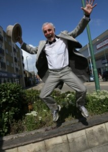 Male Pensioner in a grey suit bow tie and hat jumping in the air
