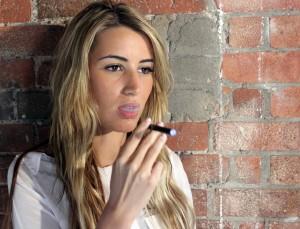 Blode girl in twenties smoking e cigerette VAT quit smoking products is 5%