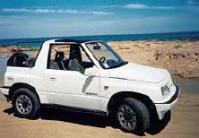 white suzuki vitara on beach